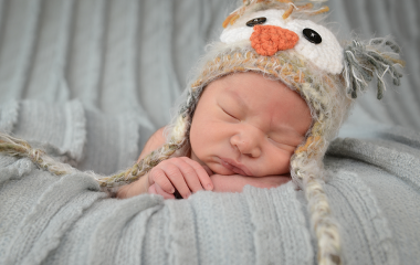 Newborn baby photographed on blanket with knit owl hat