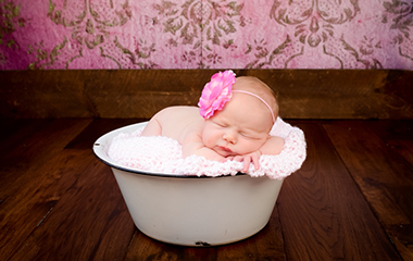 Newborn photograph of baby girl in vintage wash basin with vintage wallpaper backdrop and pink flower headband.