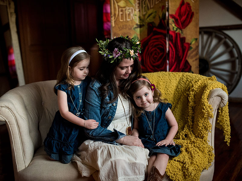 Family portrait of mother and two young daughters on vintage couch with floral crowns by Southern Pennsylvania and Philadelphia family photographer Tara Lynn of Silver Orchid Photography