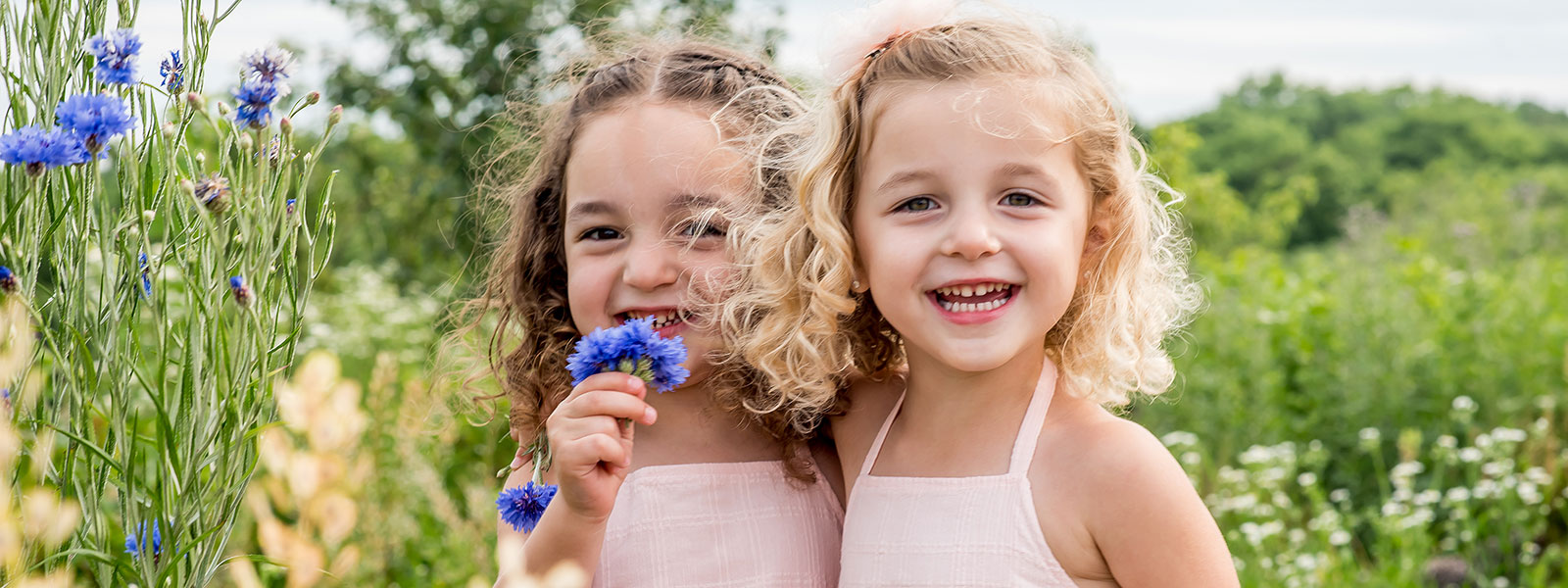 Photo of sisters in a meadow by Southern Pennsylvania and Philadelphia family photographer Tara Lynn of Silver Orchid Photography